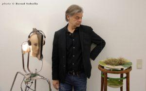 """Tom Albrecht initierte die Gründung von Group Global 3000 im Jahr 2012. Hier zwischen zwei Objekten während der Ausstellung """"Stille""""."""