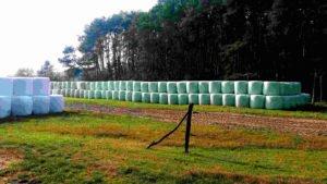 Lange Stapel von Heuballen in Plastik verpackt. Bauer sucht Industrie.